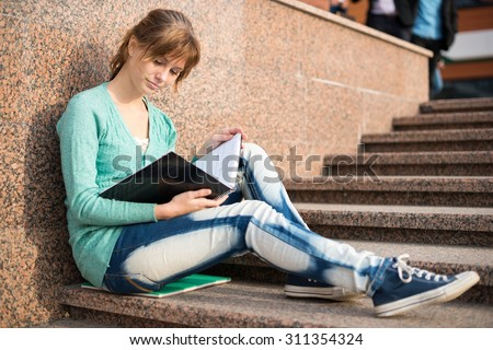 Portrait of a beautiful teenage student girl sitting on stairs in park with copy book and studing. Sunny summer day. Modern and casual lifestyle. Woman with note pad. - stock photo
