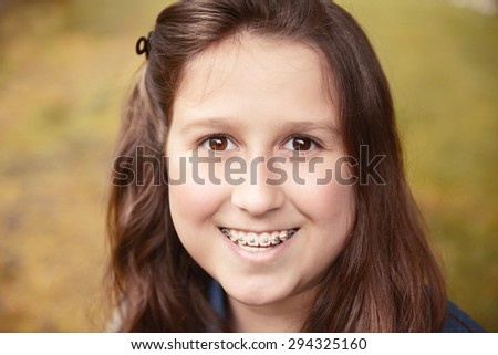 portrait of a beautiful teenager girl with long hair on nature,toned image - stock photo
