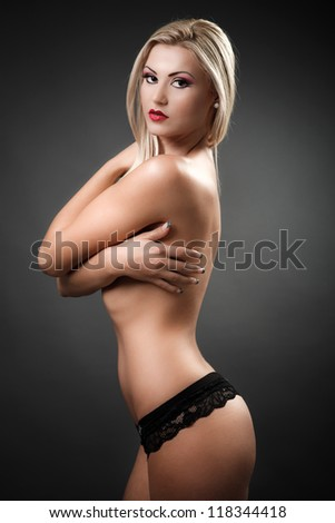 Portrait of a beautiful topless woman covering her breasts with her arms - stock photo
