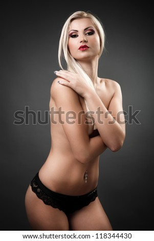 Portrait of a beautiful topless woman covering her breasts with her arms
