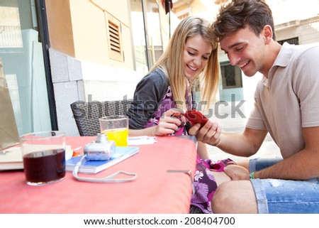 Portrait of a beautiful tourist couple sitting together at a cafe terrace with refreshments and shopping bags, visiting a destination city and using smartphone outdoors. Technology travel lifestyle. - stock photo
