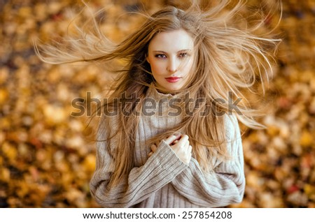 Portrait of a beautiful very cute girl with long straight hair, which flutter in the wind ; knitted sweater in autumn - stock photo