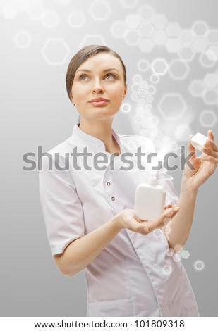 Portrait of a beautiful woman doctor presenting new medicine in blank white bottle.