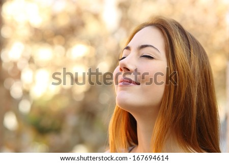 Portrait of a beautiful woman doing breath exercises with an autumn unfocused background - stock photo