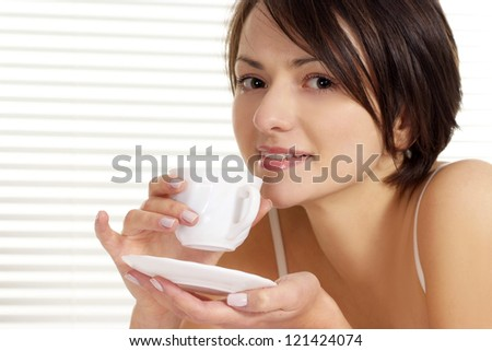 portrait of a beautiful woman drinking tea - stock photo