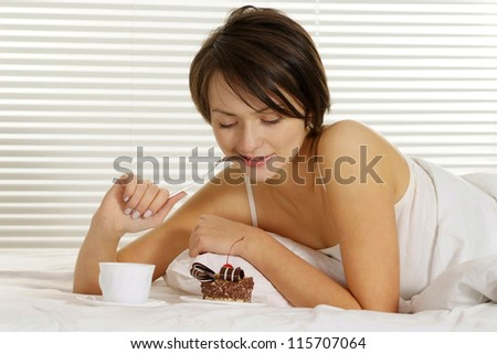 portrait of a beautiful woman eating cake on a white bed - stock photo