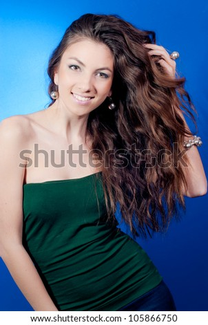 Portrait of a Beautiful woman excited and happy smiling presenting or showing hand touching her hair  in studio on the blue background - stock photo