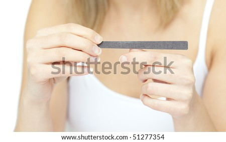 Portrait of a beautiful woman filing her nails against a white background