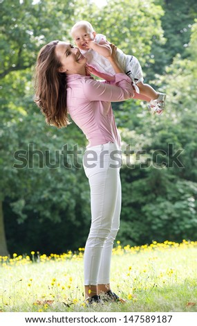 Portrait of a beautiful woman holding baby in park