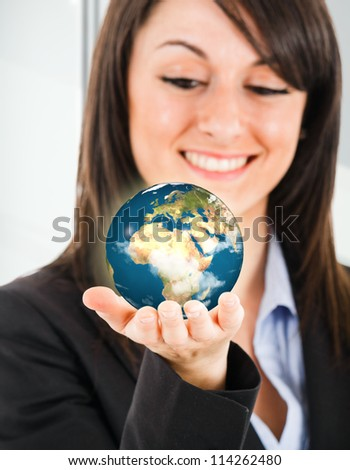 Portrait of a beautiful woman holding the world in her hand