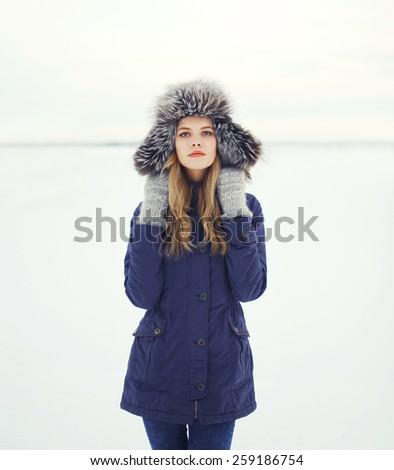 Portrait of a beautiful woman in a fur hat, winter field - stock photo