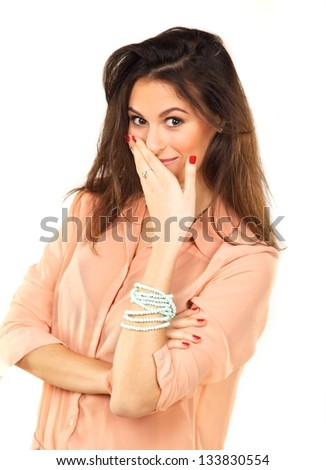 Portrait of a beautiful woman in a studio covering her mouth with her hand - stock photo