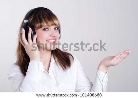 portrait of a beautiful woman in a white blouse, listening to music and happy - stock photo