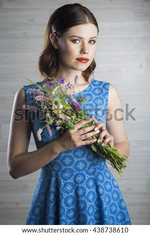 Portrait of a beautiful woman in blue dress with flowers