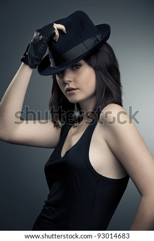portrait of a beautiful woman in fashionable hat on a dark background