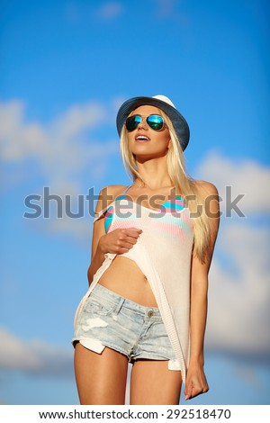 Portrait of a beautiful woman in glasses on the beach