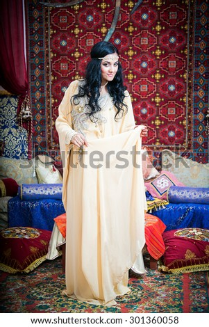 Portrait of a beautiful woman in oriental dress. Grace and beauty.Young girl in a beige dress expensive Arabic - stock photo