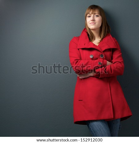 Portrait of a beautiful woman in red winter jacket on gray background - stock photo