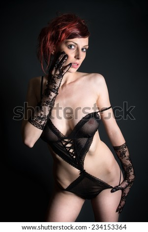 Portrait of a beautiful woman in sexy lingerie in front of black background - stock photo