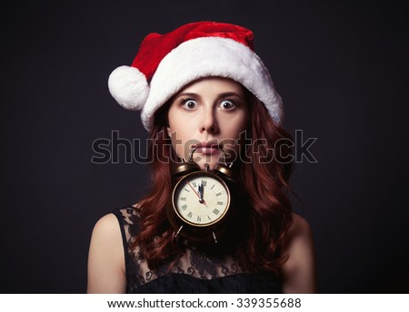 Portrait of a beautiful woman in style dress and Santa Claus with vintage alarm clock hat on dark background