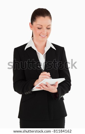 Portrait of a beautiful woman in suit writing on a notebook while standing against a white background - stock photo
