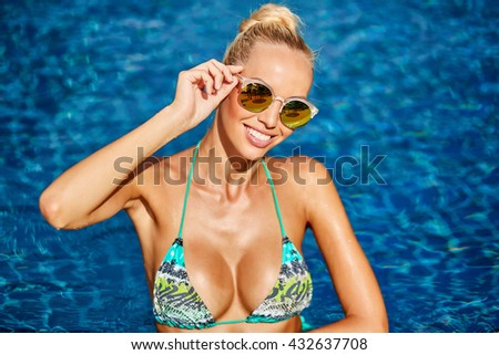 Portrait of a beautiful woman in swimming pool - stock photo