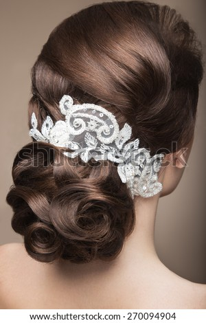 Portrait of a beautiful woman in the image of the bride with lace in her hair. Picture taken in the studio on a grey background. Beauty face.Hairstyle back view - stock photo