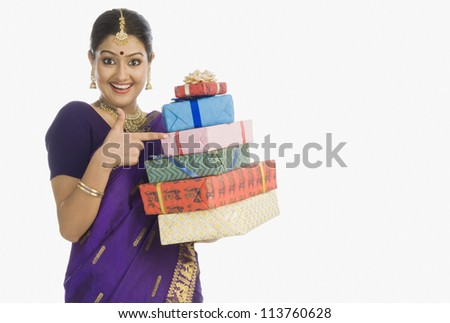 Portrait of a beautiful woman in traditional Assamese dress holding gifts and smiling - stock photo