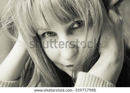 Portrait of a beautiful woman. Large eyes and blonde hair. She holds a finger near the face. Black and white picture. - stock photo
