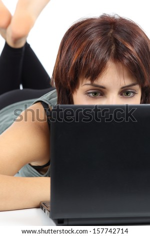 Portrait of a beautiful woman lying and browsing social media in her netbook isolated on a white background          - stock photo