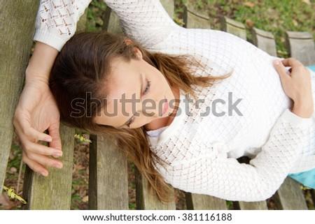 Portrait of a beautiful woman lying down on hammock outdoors - stock photo