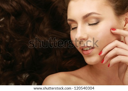Portrait of a beautiful woman lying on bed - stock photo