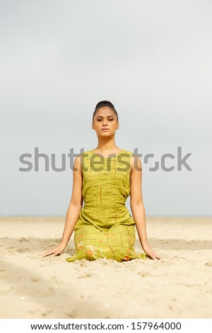 Portrait of a beautiful woman meditating at the beach - stock photo