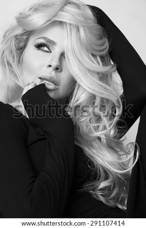 portrait of a beautiful woman on a white background and long curly blond hair and a sensual mouth with long lashes, wearing a black dress with long sleeves - stock photo