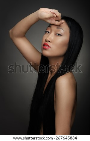 Portrait of a beautiful woman on black studio background - stock photo