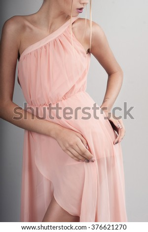 Portrait of a beautiful woman on white background in pastel pink apricot dress