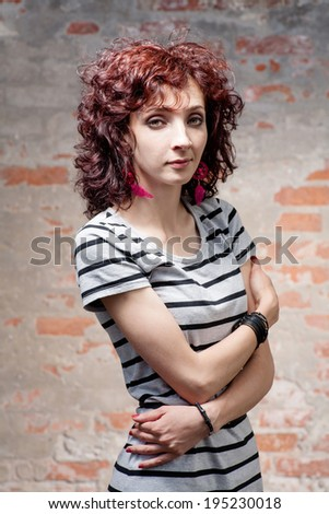 Portrait of a beautiful woman outdoors against brick wall with spot of light