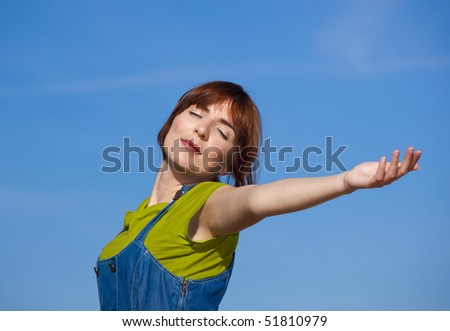 Portrait of a beautiful woman over a blue sky with arms open