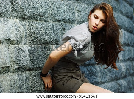 Portrait of a beautiful woman posing at the city street in sunset back light - stock photo
