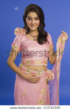 Portrait of a beautiful woman posing in traditional pink dress
