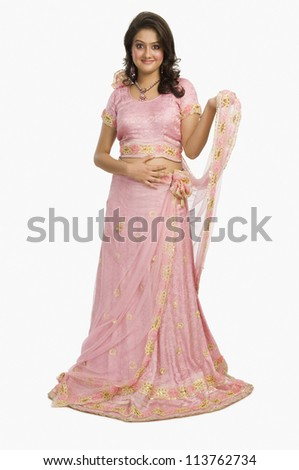 Portrait of a beautiful woman posing in traditional pink dress - stock photo