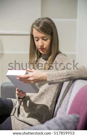 Portrait of a beautiful  woman reading a book while relaxing at home. Lovely young woman reading a book