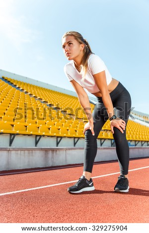 Portrait of a beautiful woman resting after run on stadium - stock photo