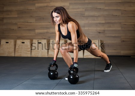 Portrait of a beautiful woman resting during her fitness exercise with a kettlebell - stock photo