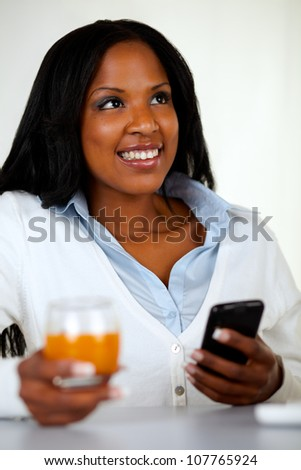 Portrait of a beautiful woman smiling while is using a cellphone and looking up at soft composition - stock photo