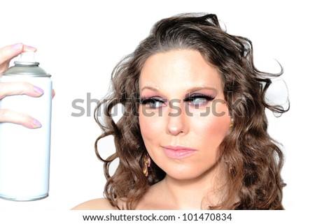 Portrait of a beautiful woman spraying hairspray - stock photo