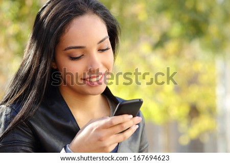 Portrait of a beautiful woman typing on the smart phone in a park with a green unfocused background
