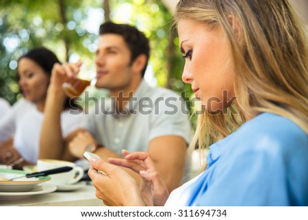 Portrait of a beautiful woman using smartphone while sitting in outdoor restaurant with friends - stock photo