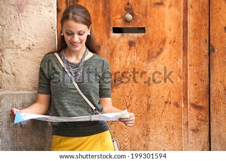 Portrait of a beautiful woman visiting a characterful destination city on holiday, smiling leaning on a textured wooden door and stone wall, holding and reading a map. Travel and tourism lifestyle. - stock photo
