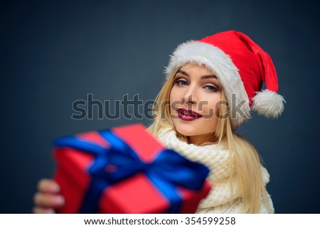 Portrait of a beautiful woman wearing a santa hat holding christmas gift box .